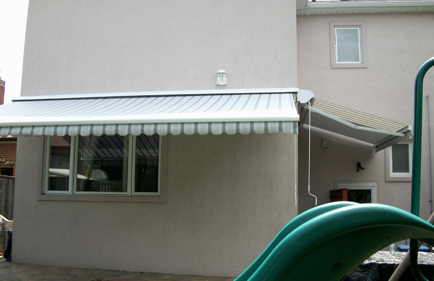 Two awnings installed on stucco wall